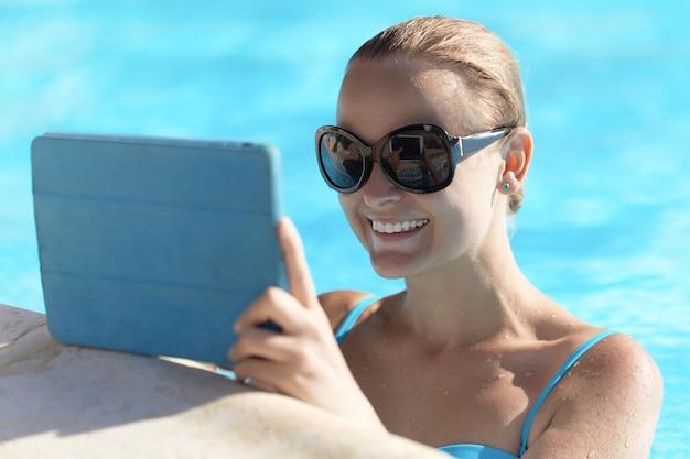 Mujer joven en una piscina con tableta