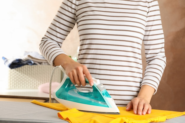 Mujer joven planchando camiseta amarilla,