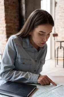 Mujer joven planeando un viaje en un café