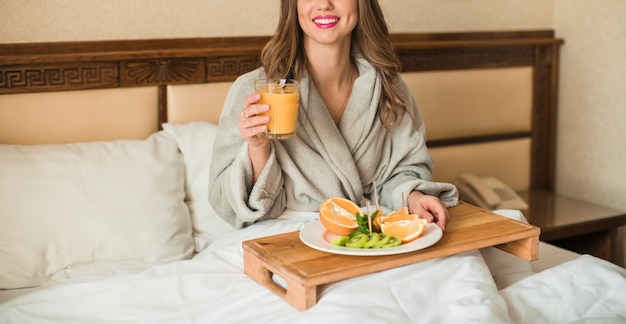 Mujer joven con plato de frutas y jugo de naranja en bandeja de madera