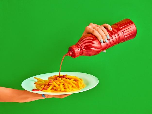 Mujer joven con plato de papas fritas y salsa de tomate