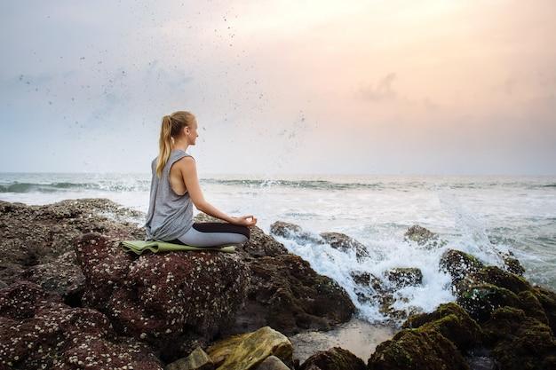 Mujer joven en la playa practica yoga a la orilla del mar durante la puesta de sol