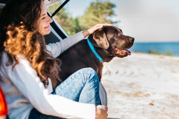 Mujer joven en la playa con su perro