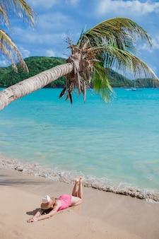 Mujer joven en una playa tropical con sombrero
