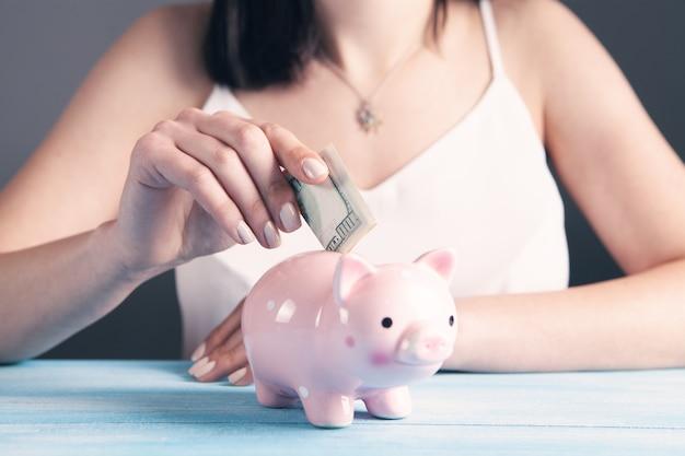 Mujer joven pone un billete de un dólar en una alcancía