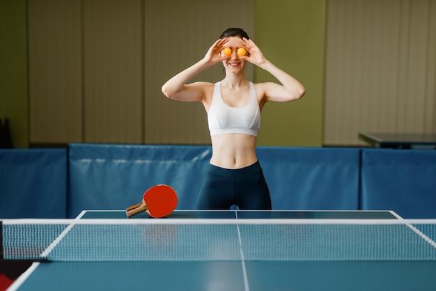 Mujer joven pone pelotas de ping pong a sus ojos en el interior.