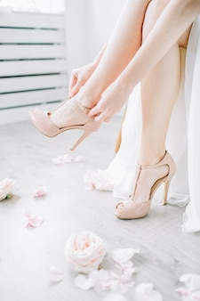 Mujer joven se pone zapatos de tacón de color rosa en una habitación luminosa con capullos de rosa