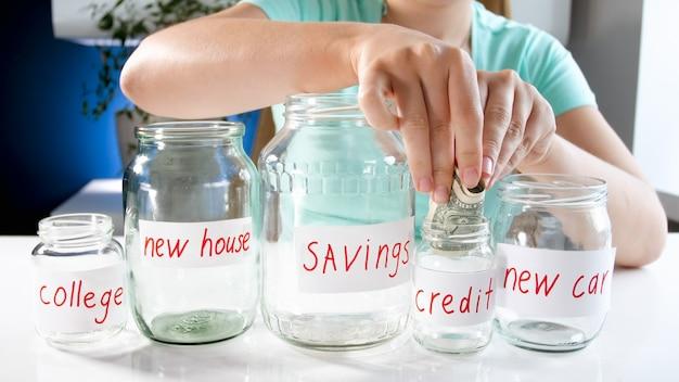 Mujer joven poniendo dinero en frasco de vidrio para ahorros crediticios. concepto de inversión financiera, crecimiento económico y ahorro bancario.