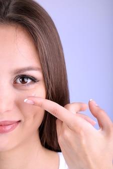 Mujer joven poniendo lentes de contacto en su ojo de cerca