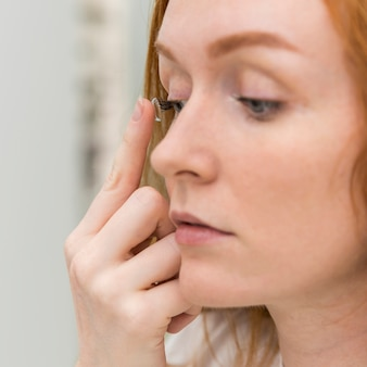 Mujer joven poniendo lentes de contacto en su ojo