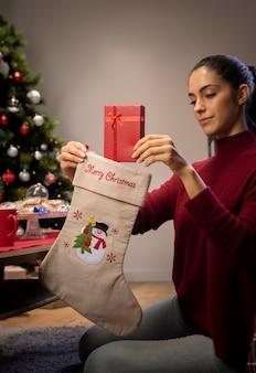 Mujer joven poniendo regalos en medias gigantes
