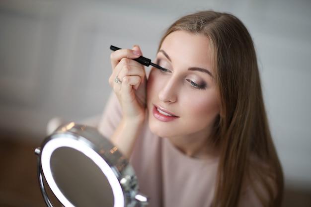 Mujer joven poniéndose maquillaje.