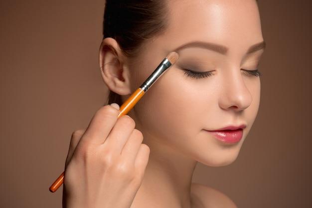 Mujer joven poniéndose maquillaje