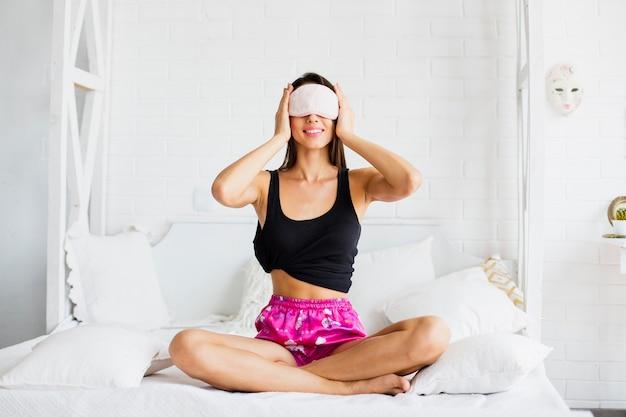 Mujer joven poniéndose máscara para dormir antes de dormir