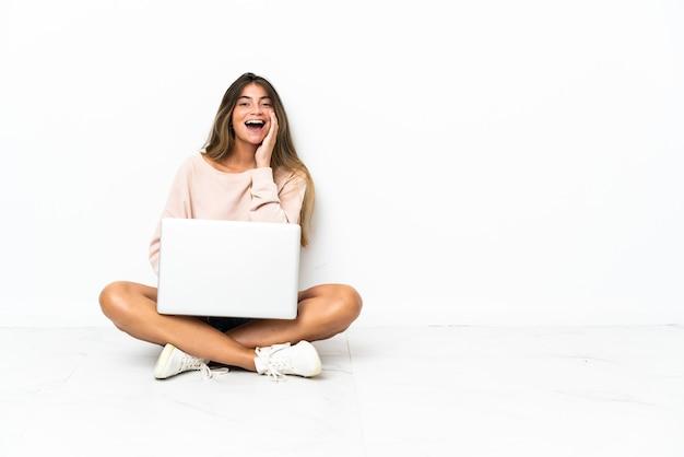 Mujer joven con un portátil sentado en el suelo aislado en blanco gritando con la boca abierta