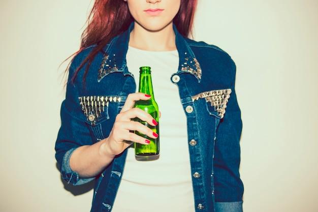Mujer joven posando con una cerveza