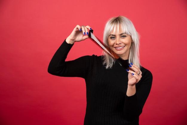Mujer joven posando con una cinta fotográfica sobre un fondo rojo. foto de alta calidad