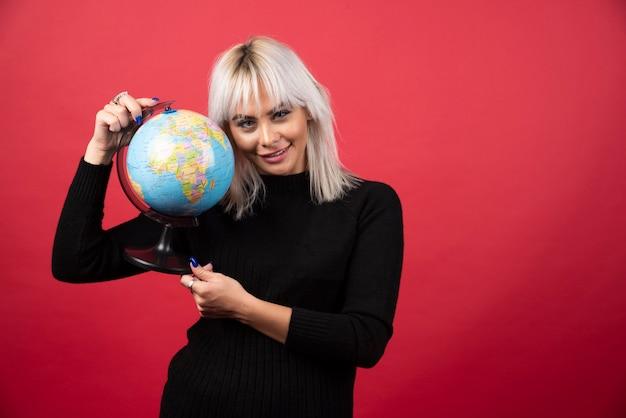 Mujer joven posando con un globo sobre un fondo rojo. foto de alta calidad