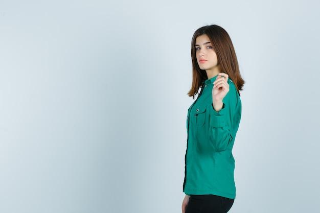 Mujer joven posando mientras levanta la mano en camisa verde y se ve fascinante.