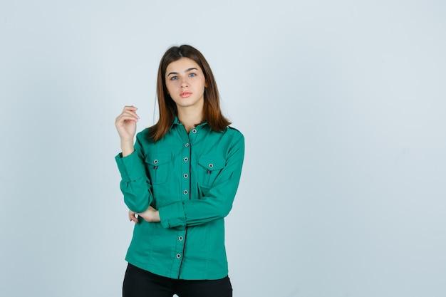 Mujer joven posando mientras está de pie en camisa verde y mirando sensible, vista frontal.