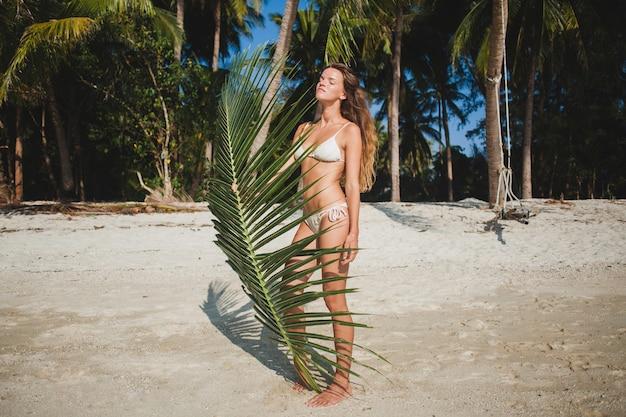 Mujer joven posando en la playa de arena bajo la hoja de palmera
