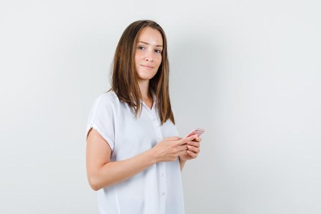 Mujer joven posando con teléfono en blusa blanca y mirando tranquilo.