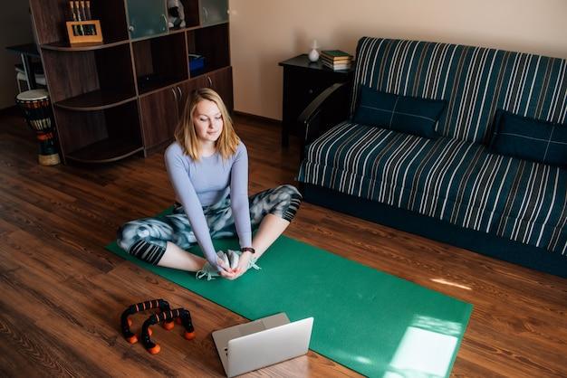 Mujer joven en pose de yoga viendo clases en línea en la habitación