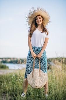 Mujer joven, posición, con, bolsa, en, sombrero grande, en, campo