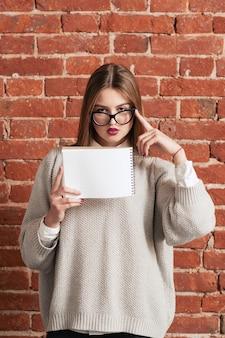 Mujer joven, posición, con, cuaderno en blanco