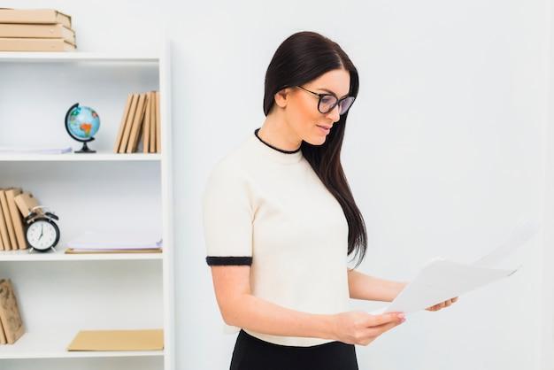 Mujer joven, posición, con, papeles, en, oficina