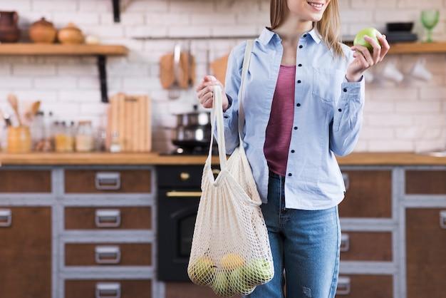 Mujer joven positiva con bolsa reutilizable con frutas eco