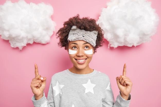 Mujer joven positiva con cabello rizado usa antifaz y traje de dormir aplica parches de belleza debajo de los ojos puntos arriba en nubes blancas anuncia producto para dormir tiene buen humor