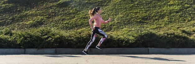 Mujer joven positiva corriendo al aire libre