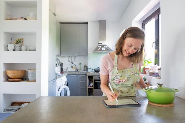 Mujer joven positiva escribiendo notas para la receta en la pantalla del pad, usando la tableta cerca de una cacerola grande en el mostrador. vista frontal, espacio de copia. cocinar en casa e internet concepto