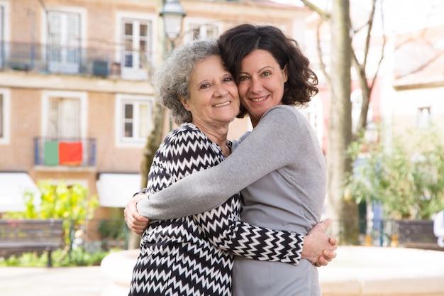 Mujer joven positiva feliz que presenta con su mamá