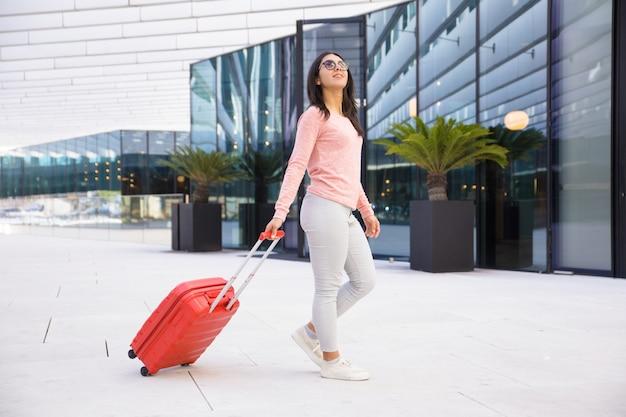 Mujer joven positiva en las gafas de sol que salen del pasillo del aeropuerto
