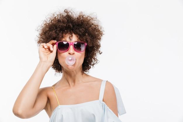 Mujer joven positiva en gafas de sol que sopla burbujas
