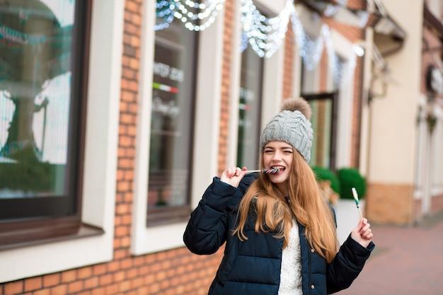 Mujer joven positiva en gorro de punto comiendo coloridos dulces navideños en el fondo borroso