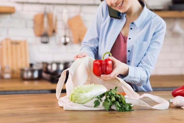 Mujer joven positiva orgullosa de comestibles orgánicos