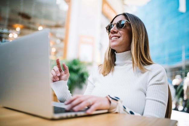 Mujer joven positiva pensativa que usa el ordenador portátil en la tabla en café de la calle