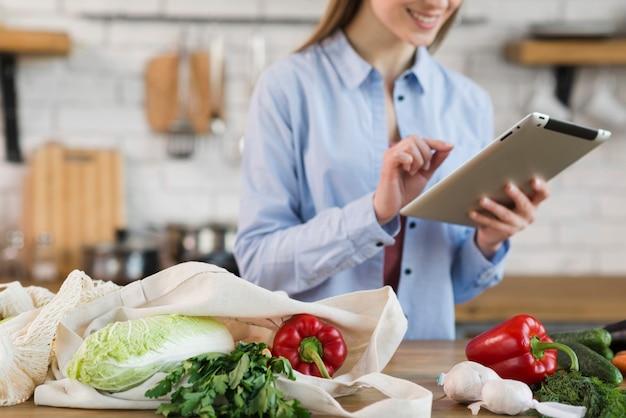 Mujer joven positiva que comprueba la lista de compras en la tableta