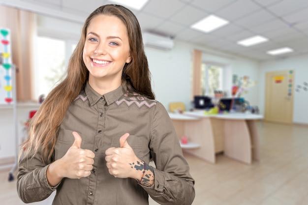Mujer joven positiva que expresa felicidad y que muestra ok