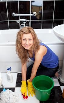 Mujer joven positiva que limpia el piso del cuarto de baño