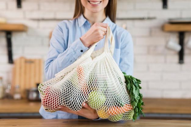 Mujer joven positiva que sostiene la bolsa reutilizable con verduras