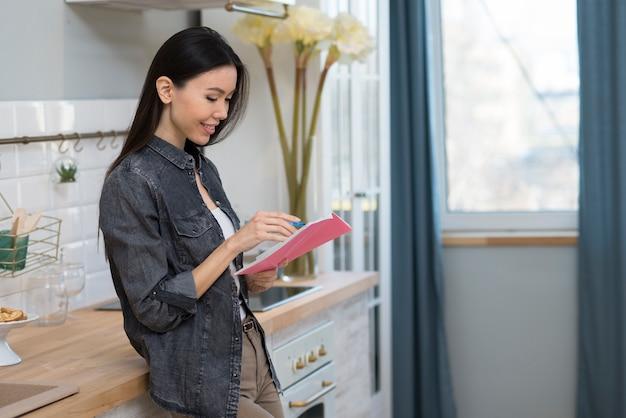 Mujer joven positiva que toma notas en la cocina