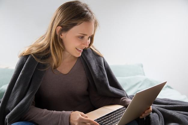 Mujer joven positiva que usa la computadora portátil en dormitorio