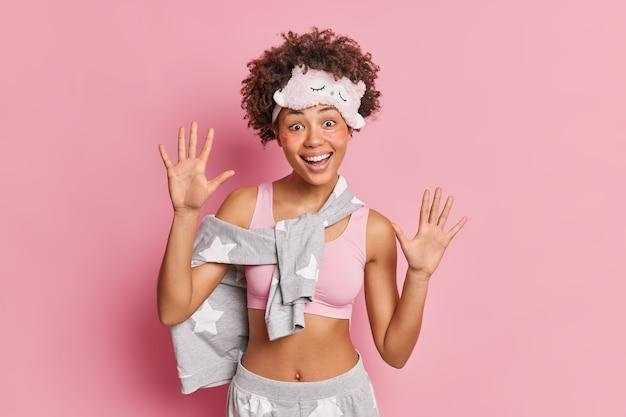 Mujer joven positiva en ropa doméstica levanta las palmas de las manos se divierte se prepara para dormir aplica parches de colágeno debajo de los ojos posa contra la pared rosa