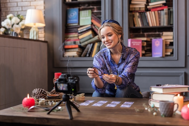 Mujer joven positiva sosteniendo una cadena de cuentas mientras se lo muestra a la cámara