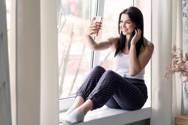 Mujer joven positiva tomando un selfie