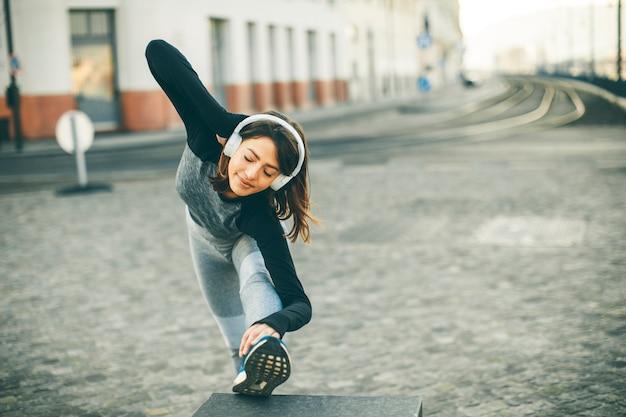 La mujer joven practica estirar después de correr al aire libre